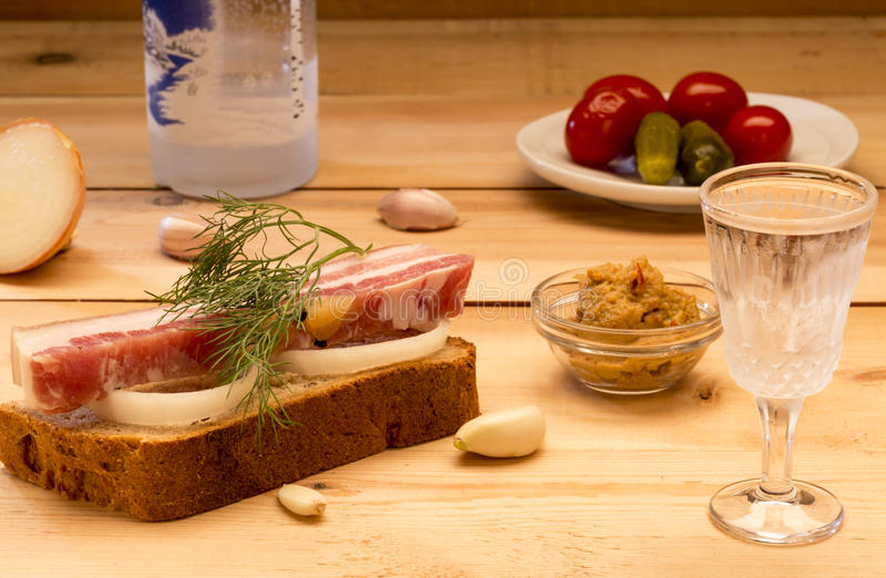 Sandwich with spiced lard served with garlic, onions, mustard, pickles, tomatoes and cold vodka royalty free stock images
