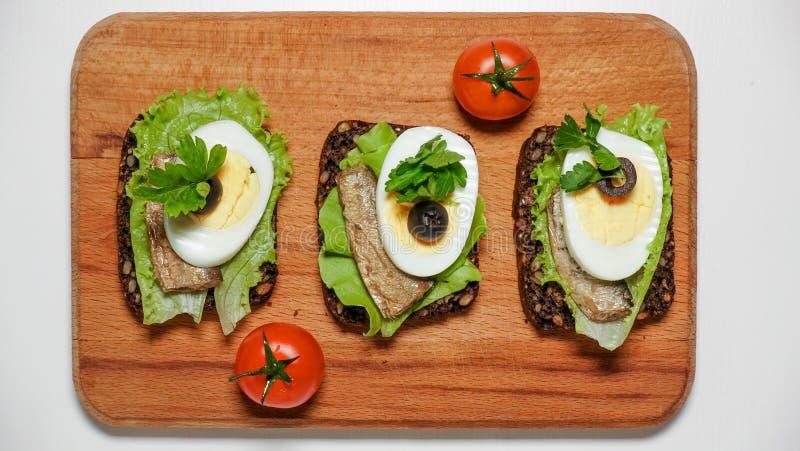 Sandwich sur le pain noir avec l'oeuf et les sardines photos libres de droits