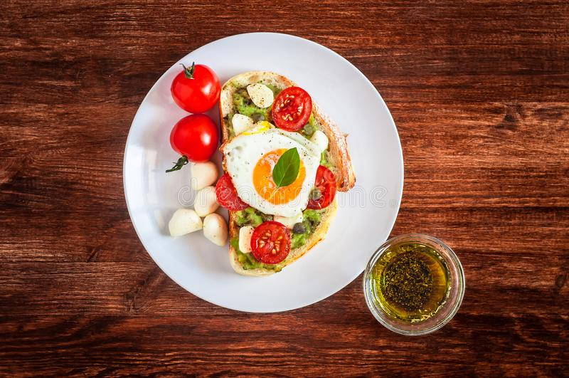 Sandwich toasts with agg, tomatoes cherry, mozzarella, avocado, basil and olive oil. Top view on a dark wooden stock photo