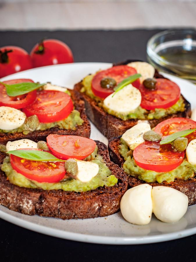Sandwich toasts with tomatoes cherry, mozzarella, avocado, basil and olive oil. Side view on a dark stone dish. stock image