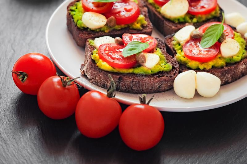Sandwich toasts with tomatoes cherry, mozzarella, avocado, basil and olive oil. Side view on a dark stone dish. royalty free stock photography