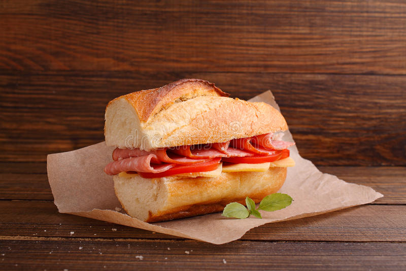 Sandwich with tomato, sausage and cheese. On a dark background stock photo