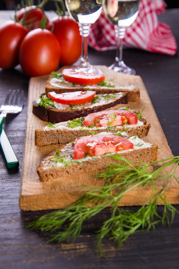 Sandwich with tomatoes. Sandwich from dark bread and fresh tomatoes on old wooden board royalty free stock photos