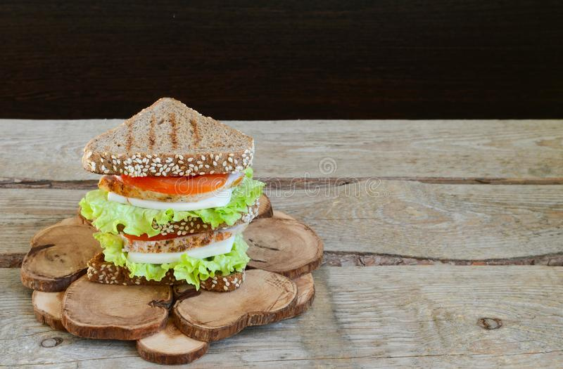 Sandwich of triangular bread with chicken breast tomato and cheese Wooden rustic background stock photography