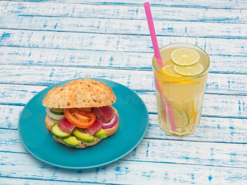 Sandwich with tuna on a plate, vegetables and a glass of lemonade stock images