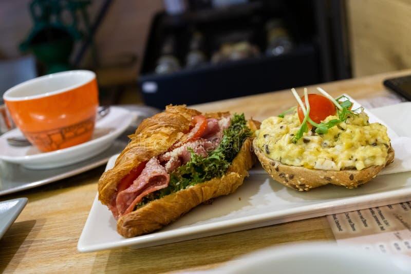 Sandwich und Kaiser mit Schinken, Salat, Käse und zertrümmerten Eiern, Kaffee im Hintergrund lizenzfreie stockfotos