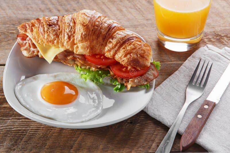 Sandwichcroissant met gebraden de tomatenontbijt en ei van de baconkaas royalty-vrije stock afbeelding