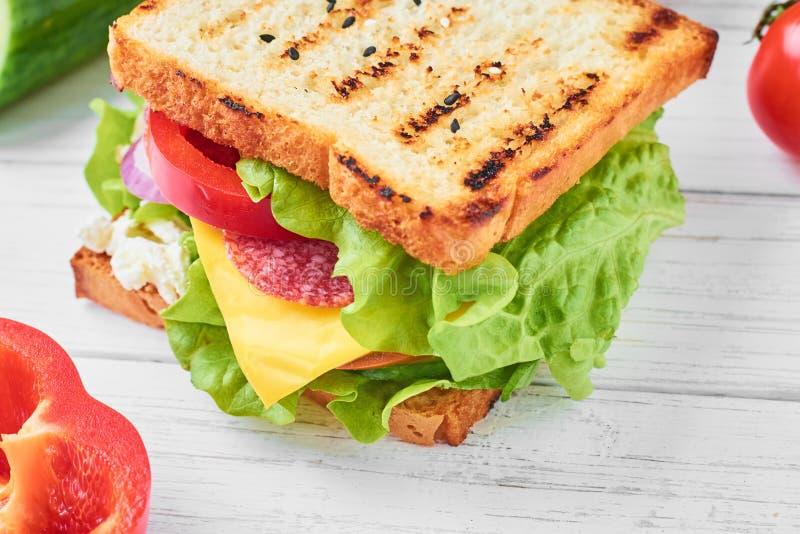 Sandwiche med skinka, grönsallat och nya grönsaker på ett vitt bakgrundsslut upp arkivbild