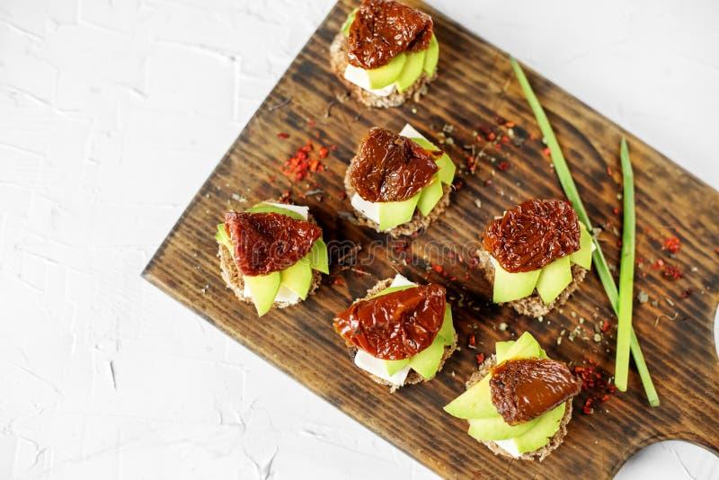 Sandwiche mit Käse, Avocado und getrockneten Tomaten auf dem Brett Konzept für Nahrung, gesunde Nahrung und Vegetarier lizenzfreies stockfoto
