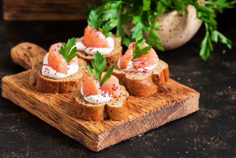 Sandwiche mit Lachsen Canape mit roten Fischen, Roggenbrot, Weichkäse, Petersilie und Gewürzen Selektiver Fokus lizenzfreie stockbilder