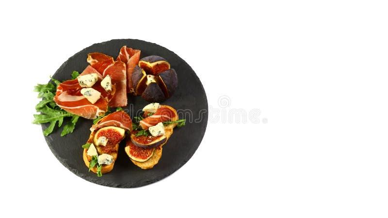 Sandwiche mit Prosciutto, frischen Feigen, dorblyu und Beeren auf einem Schieferbrett wird auf einem weißen Hintergrund lokalisie stockfotos
