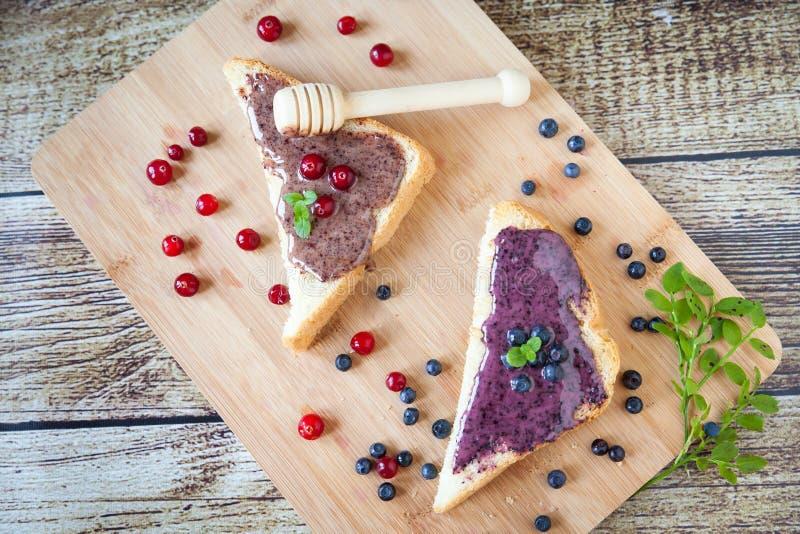 Sandwiche mit Sahne Honig, Blaubeeren und Moosbeeren lizenzfreie stockfotografie