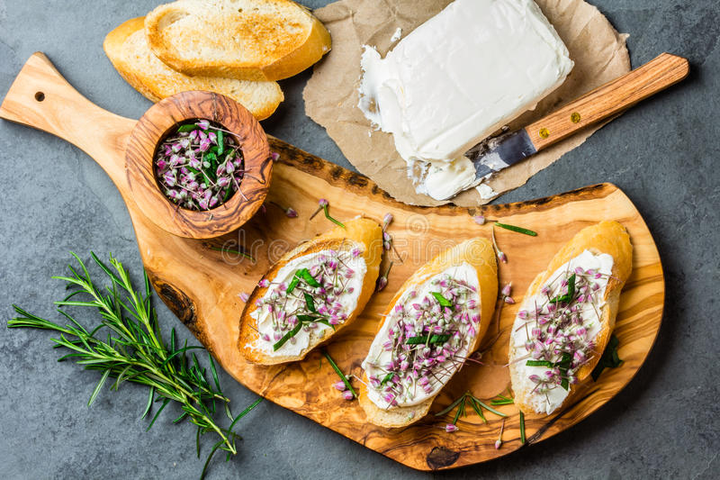 Sandwiche mit Sahne Käse und des Knoblauchs essbare Blumen, olivgrünes Brett lizenzfreie stockfotos