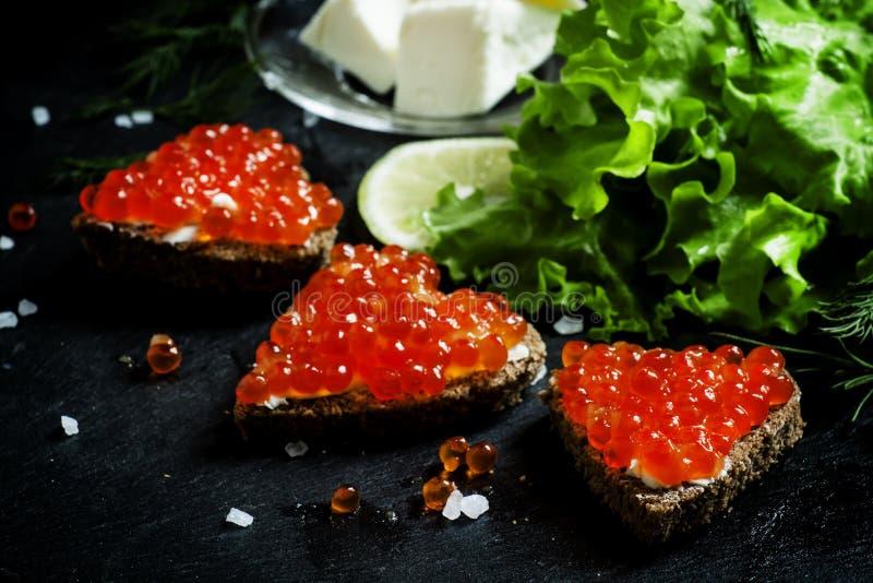 Sandwiche mit schwarzem Roggenbrot, Butter und Kaviar der roten Lachse an lizenzfreies stockbild