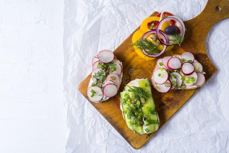 Sandwiche oder Tapas bereiteten mit Sahne Käse und Gemüse, auf Schneidebrett, über weißem Hintergrund vor Gesunde Nahrung für das lizenzfreie stockfotos