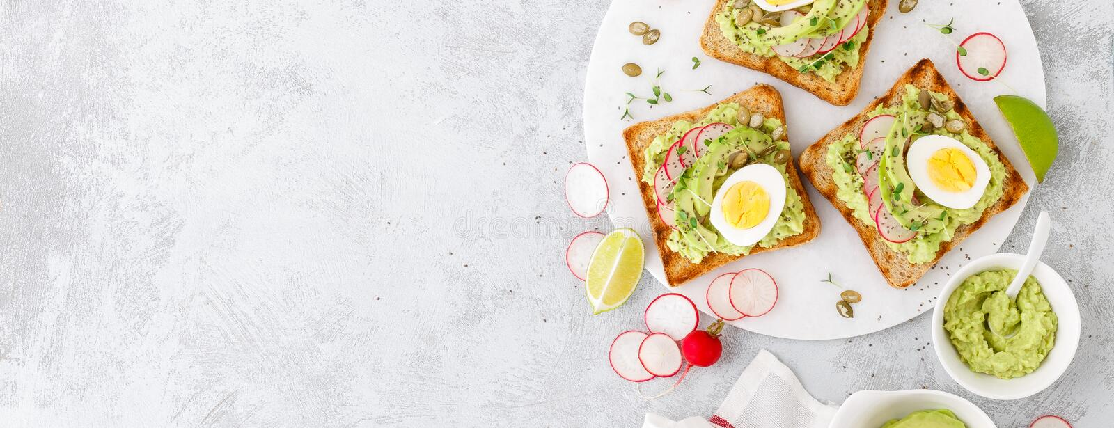 Sandwiches with avocado guacamole, fresh radish, boiled egg, chia and pumpkin seeds. Diet breakfast. Delicious and healthy plant-b. Ased trend food. Flat lay stock images