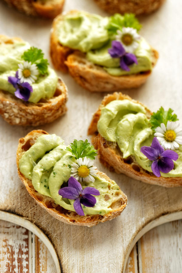 Sandwiches with avocado paste with the addition of edible flowers stock photos