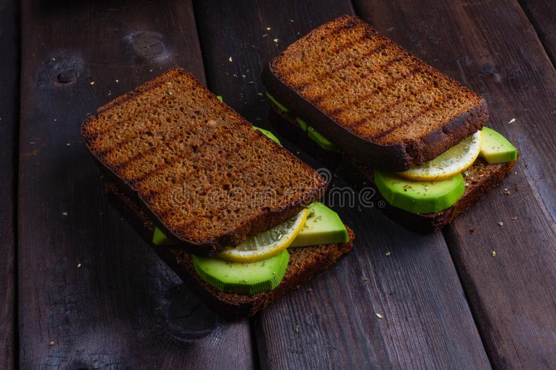 Sandwiches with avocado on a wooden dark background stock photography