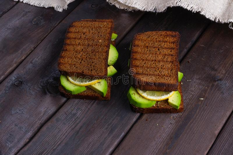 Sandwiches with avocado on a wooden dark background royalty free stock images