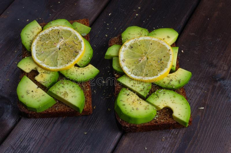 Sandwiches with avocado on a wooden dark background stock photos