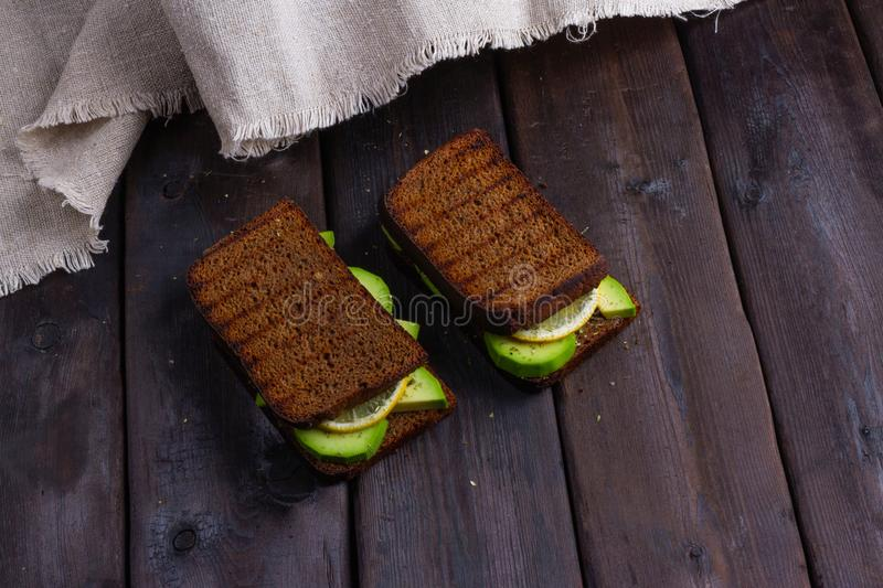 Sandwiches with avocado on a wooden dark background royalty free stock image