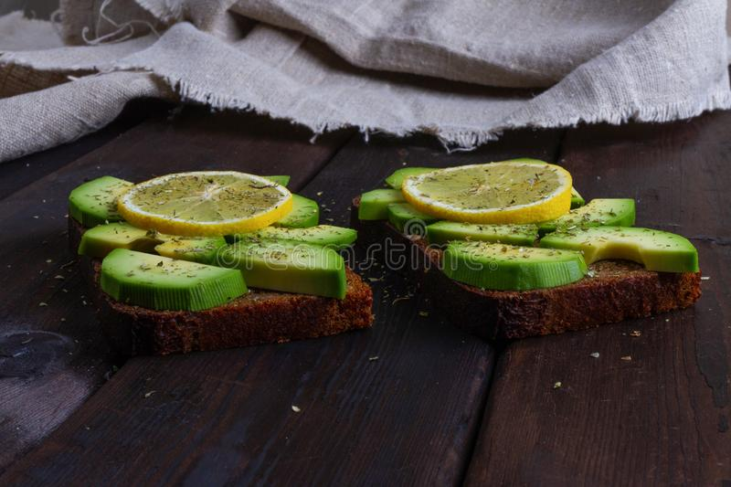 Sandwiches with avocado on a wooden dark background stock image