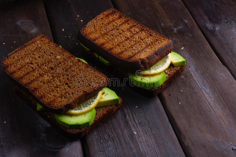 Sandwiches with avocado on a wooden dark background royalty free stock photo