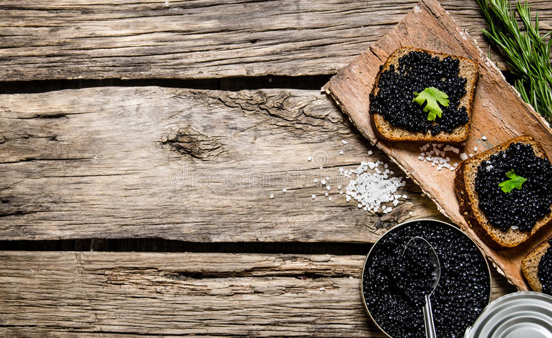 Sandwiches with black caviar, a jar of caviar and spoon. royalty free stock photos