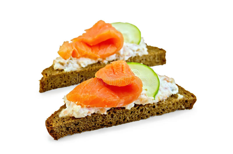 Sandwiches on bread with salmon and cucumber. Toast two slices of rye bread with cream, salmon and cucumber with a light shade on white background royalty free stock image