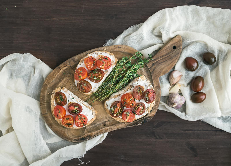 Sandwiches (brushtta) with roasted cherry tomatoes, soft cheese, royalty free stock images