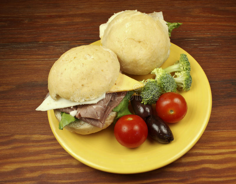 Sandwiches on a bun. Yeollow plate, and table with tomatoes, olives, and brocoli stock image