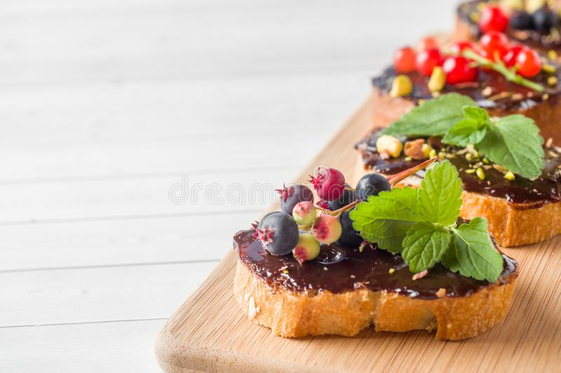 Sandwiches with chocolate paste, pistachio nuts and fresh berries on a wooden serving Board. Copy space. Sandwiches with chocolate paste, pistachio nuts and royalty free stock photography