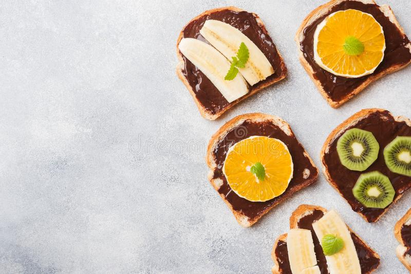 Sandwiches with chocolate paste and various fruits on a gray table. Top view. Concept delicious Breakfast. Copy space royalty free stock images