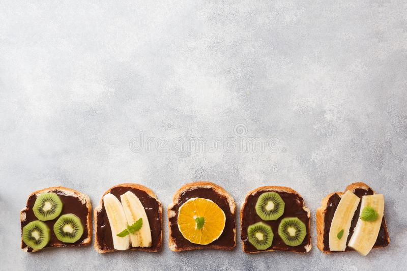 Sandwiches with chocolate paste and various fruits on a gray table. Top view. Concept delicious Breakfast. Copy space royalty free stock photography