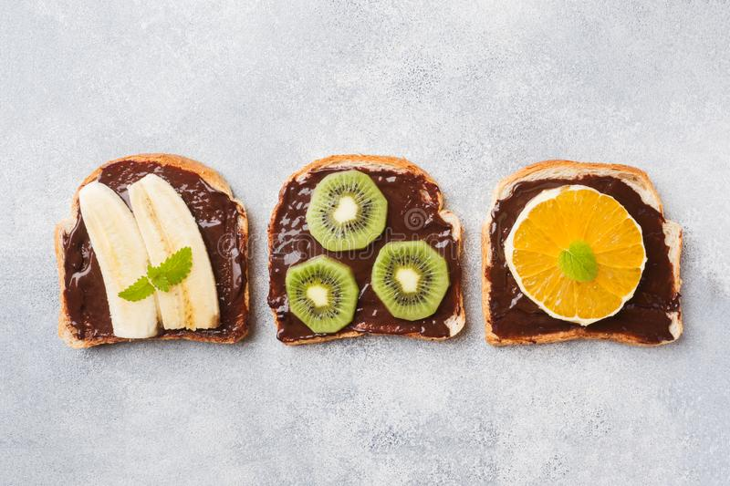 Sandwiches with chocolate paste and various fruits on a gray table. Top view. Concept delicious Breakfast stock photo