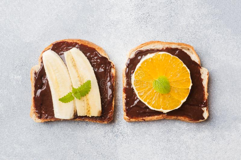 Sandwiches with chocolate paste and various fruits on a gray table. Top view. Concept delicious Breakfast royalty free stock images