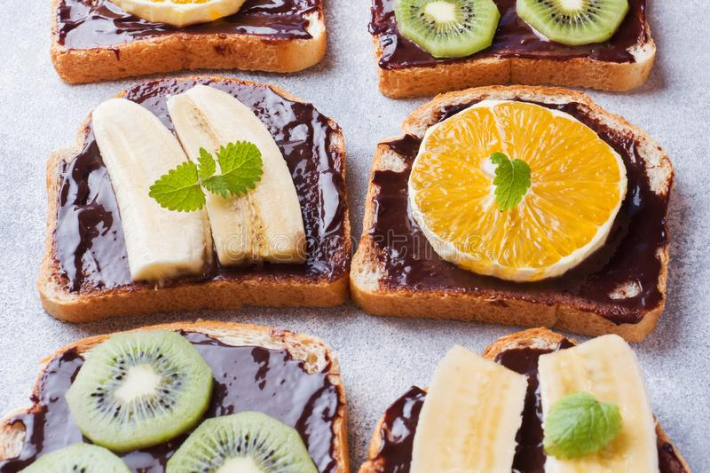 Sandwiches with chocolate paste and various fruits on a gray table. Top view. Concept delicious Breakfast royalty free stock image