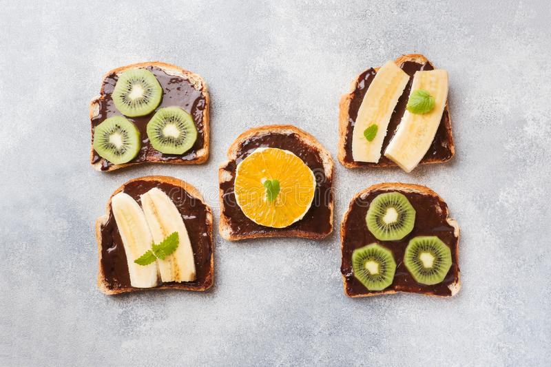 Sandwiches with chocolate paste and various fruits on a gray table. Top view. Concept delicious Breakfast stock images