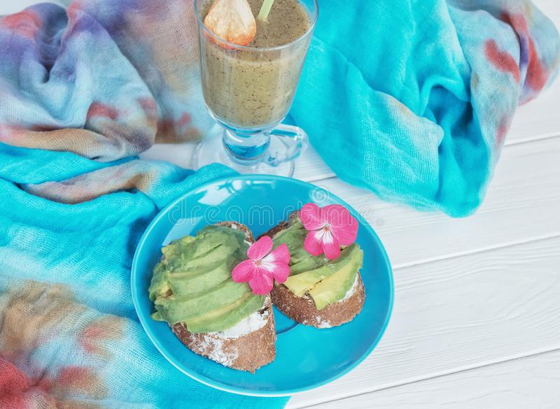 Sandwiches with coarse bread and avocado and green natural smoothies made from kiwi and greens. Healthy food. Still life, the mood. Of light summer snack royalty free stock image