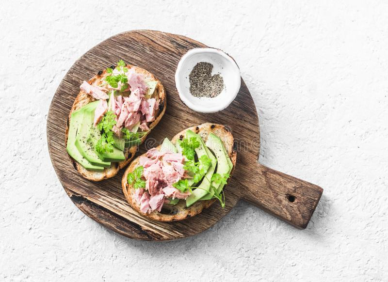 Sandwiches with cream cheese, avocado and tuna fish on wooden cutting board on white background, top view. Healthy breakfast stock images