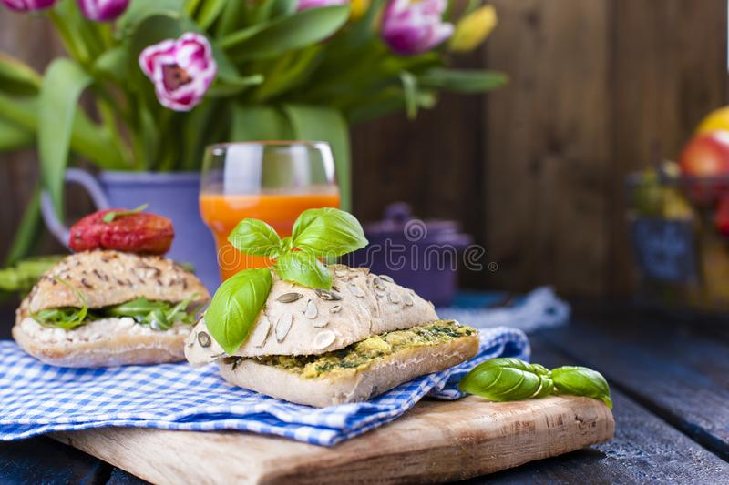 Sandwiches with fresh Italian rolls with avocado, basil, tomatoes and soft cheese. Breakfast healthy eating on a dark background. stock photos