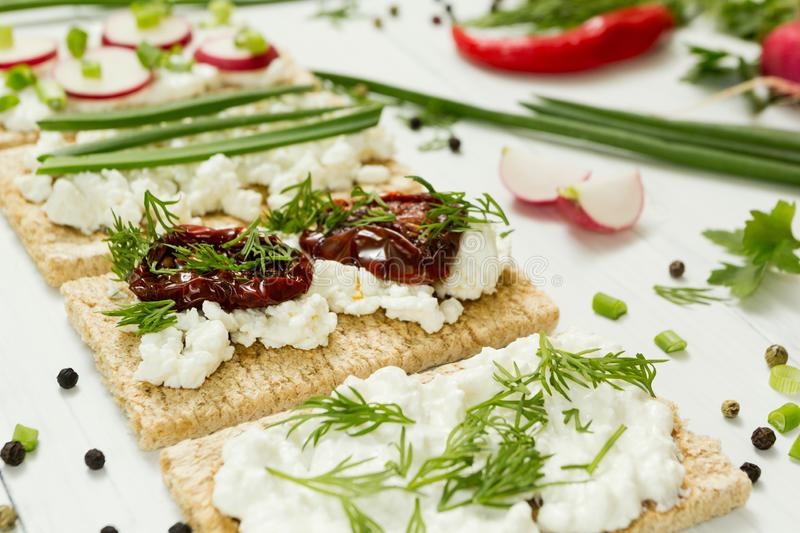 Sandwiches from goat cheese with sun dried tomatoes in olive oil with vegetables on a white wooden background stock photo