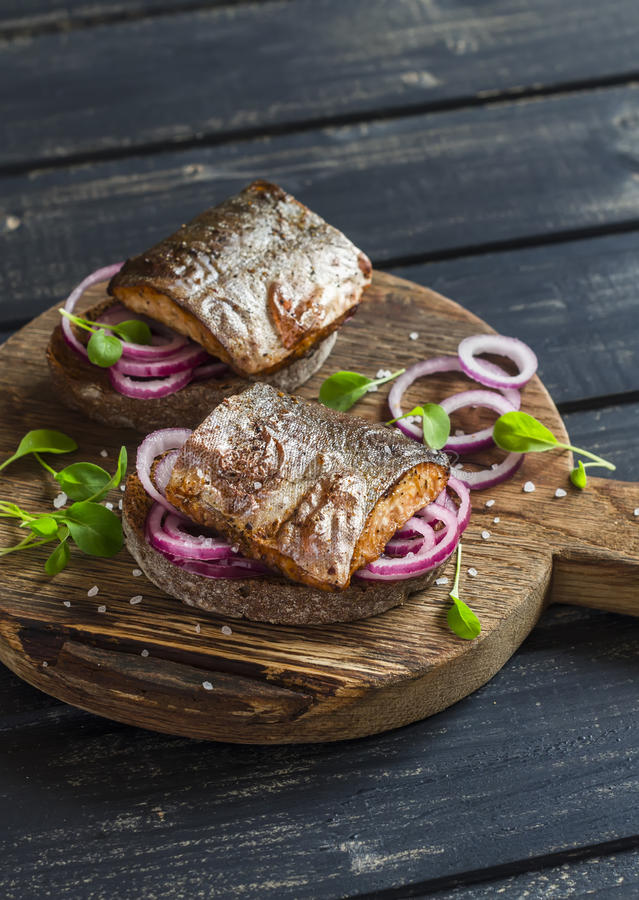 Sandwiches with grilled fish and quick pickled onions stock images