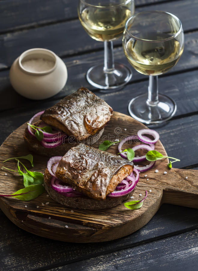 Sandwiches with grilled fish and quick pickled onions and two glasses of white wine royalty free stock photography