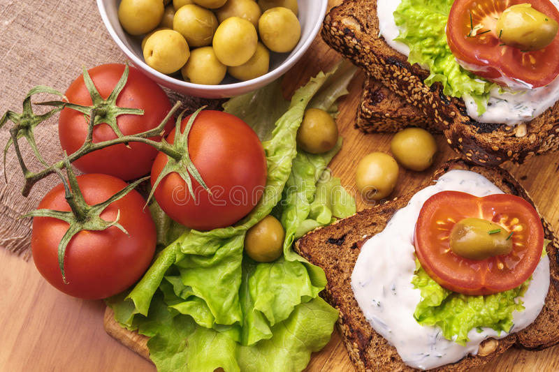 Sandwiches with healthy rye bread, cheese cream, tomatoes, green olives stock photo