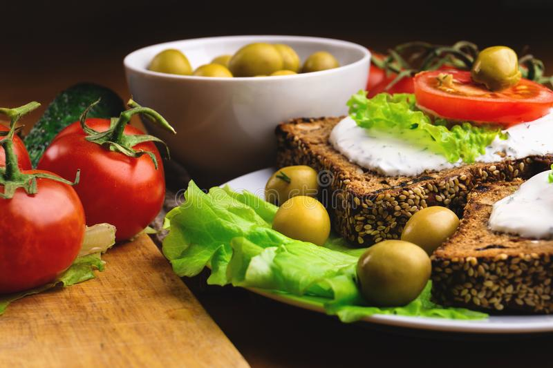 Sandwiches with healthy rye bread, cheese cream, tomatoes, green olives and lettuce on table. Healthy vegetarian food concept royalty free stock photos