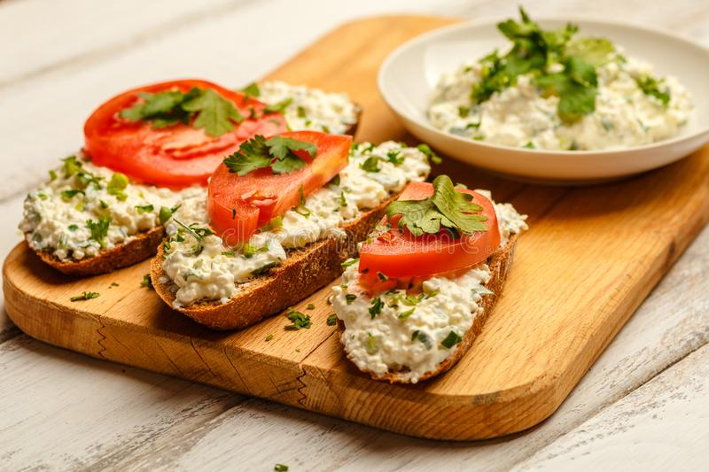 Sandwiches with healthy rye bread, cheese cream, tomatoes on white wooden table. Love for a healthy food royalty free stock photos