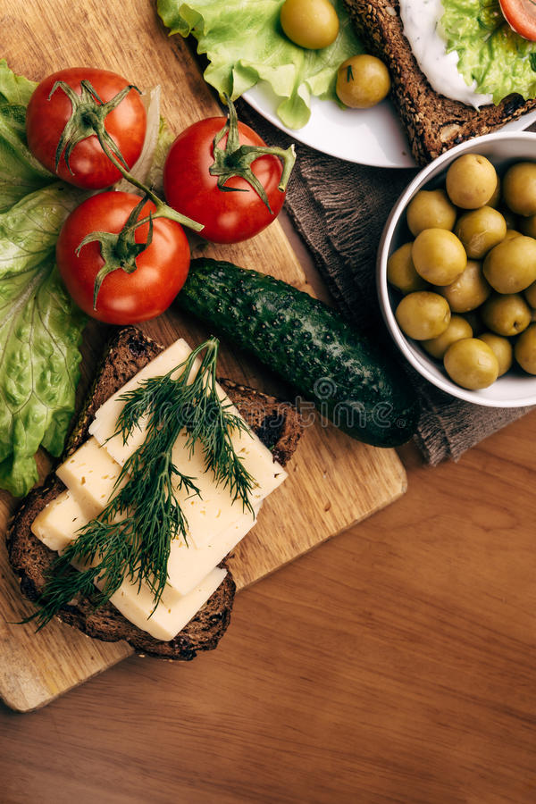 Sandwiches of homemade bread with cheese sauce or cream, lettuce, tomatoes royalty free stock photo