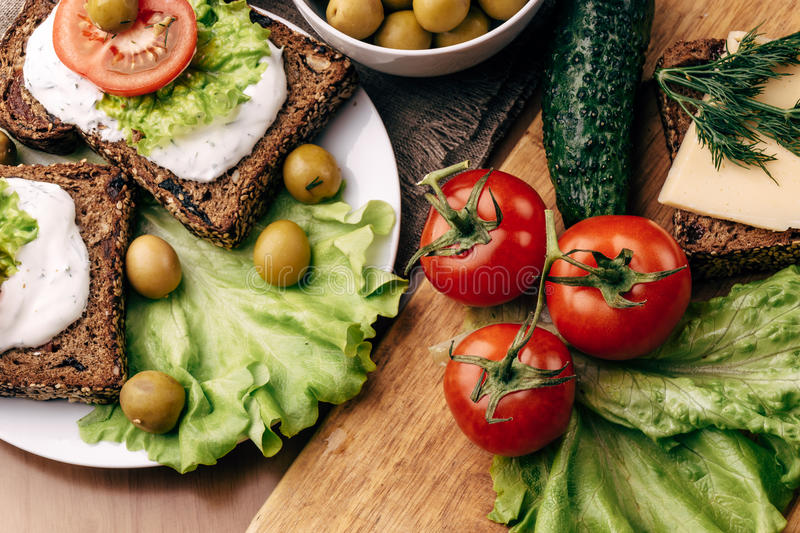 Sandwiches of homemade bread with cheese sauce or cream, lettuce, tomatoes stock photos