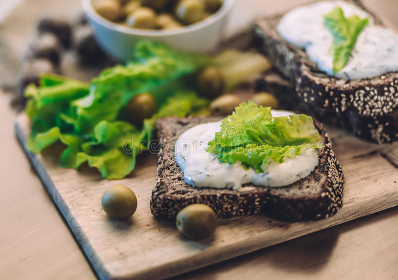 Sandwiches of homemade bread with cheese sauce or cream, lettuce, walnuts, olive royalty free stock image
